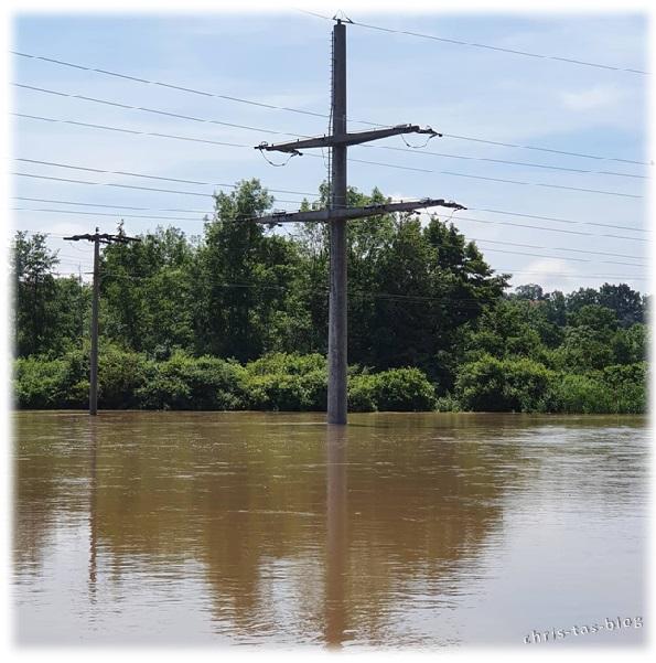 Strommast Wiesengrund unter Wasser