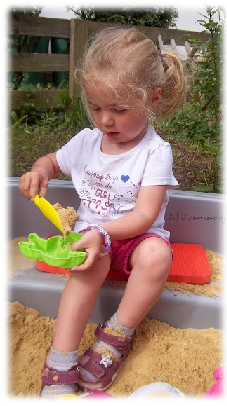 Virginia mit ihrem neuen Armband in der Sandkiste
