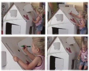 Spielhaus aus Pappkarton wird liebevoll bemalt