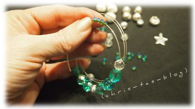 verschiedene Perlen auf den Draht auffädeln